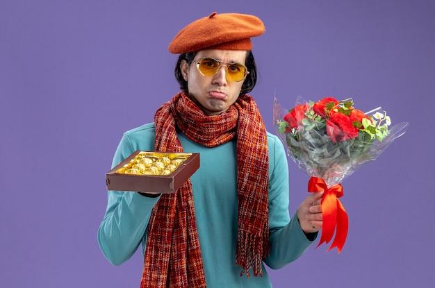 Trieste jonge kerel op valentijnsdag met hoed met sjaal en bril met boeket met doos snoep geïsoleerd op blauwe achtergrond