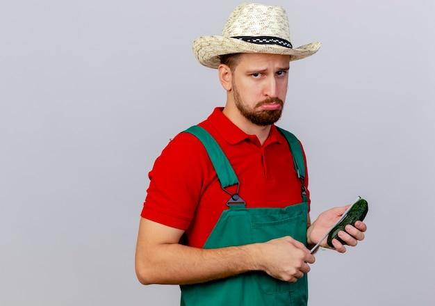 Trieste jonge knappe slavische tuinman in uniform en hoed op zoek bedrijf komkommer en meetlint komkommer meten geïsoleerd