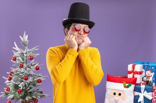 Trieste jonge man in gele coltrui en bril met zwarte hoed staande naast een kerstboom en presenteert op paarse achtergrond