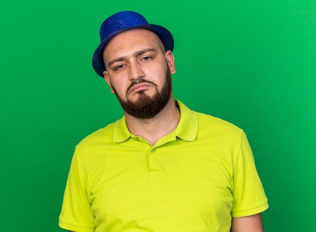 Trieste jonge man met blauwe feestmuts geïsoleerd op groene muur