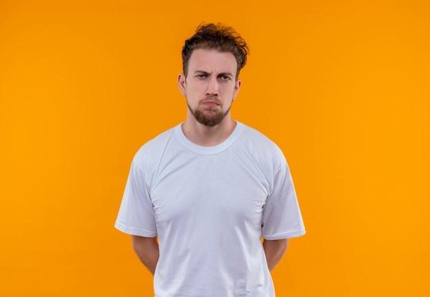 Trieste jonge man met een wit t-shirt legde zijn handen terug op geïsoleerde oranje achtergrond