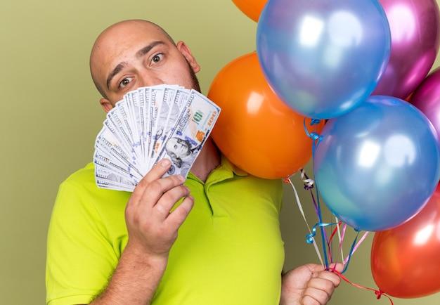 Trieste jonge man met geel t-shirt met ballonnen bedekt gezicht met geld geïsoleerd op olijfgroene muur