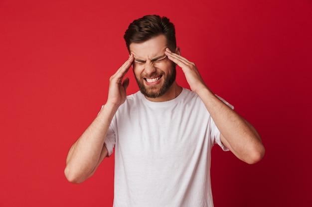 Trieste jonge man met hoofdpijn staande geïsoleerd