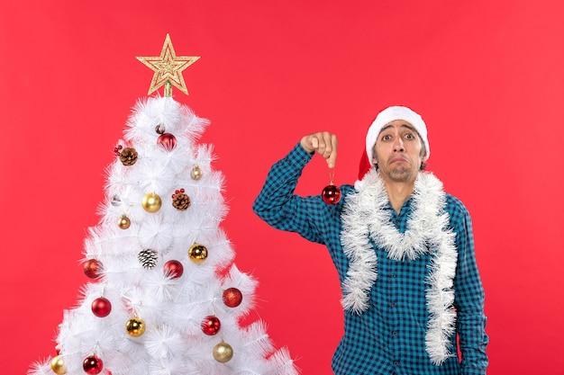 Trieste jonge man met kerstman hoed in een blauw gestreept shirt en decoratie-accessoire te houden