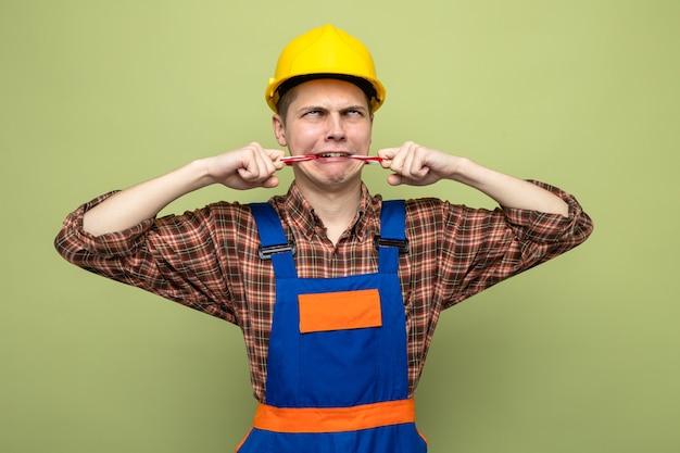 Trieste jonge mannelijke bouwer die een verzegelde mond draagt met ducttape-uniform
