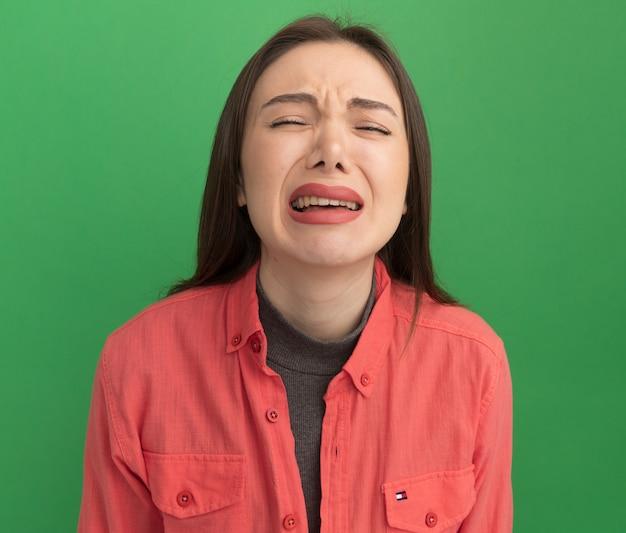 Trieste jonge mooie vrouw huilen met gesloten ogen geïsoleerd op groene muur