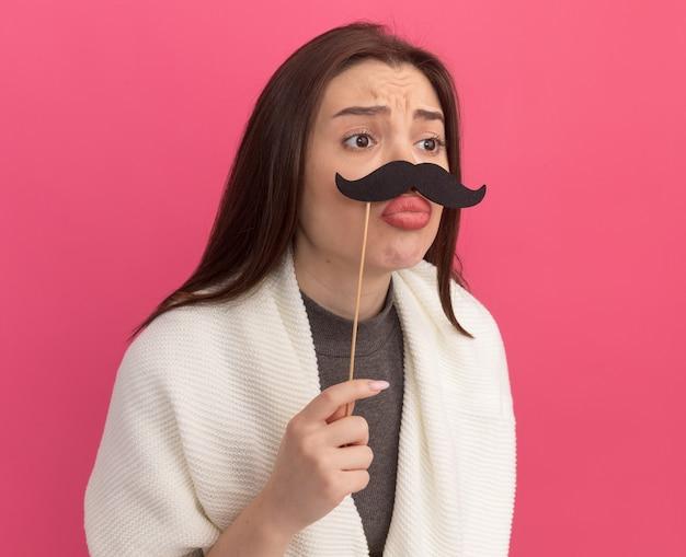Trieste jonge mooie vrouw met nep-snor op stok boven lippen kijkend naar kant met getuite lippen geïsoleerd op roze muur