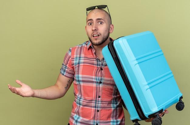 Trieste jonge reiziger man met zonnebril met koffer geïsoleerd op olijfgroene muur met kopieerruimte