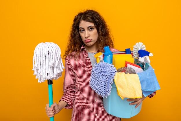 Trieste jonge schoonmaakster die dweil vasthoudt met emmer schoonmaakgereedschap