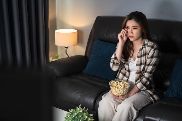 Trieste jonge vrouw die televisie kijkt en 's nachts op de bank huilt