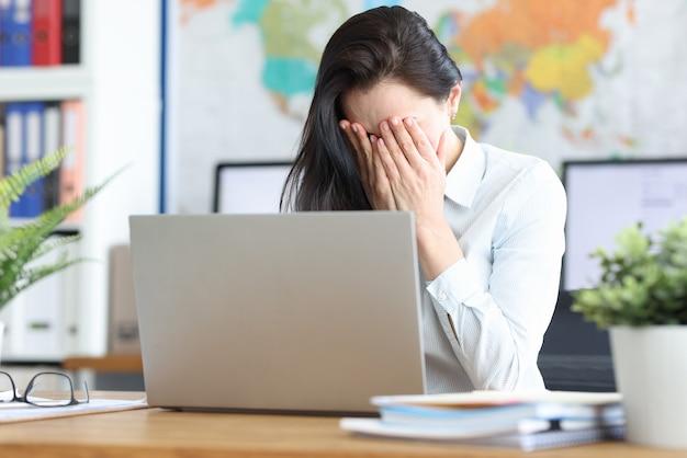 Trieste jonge vrouw zit op laptop die haar gezicht bedekt met haar handen