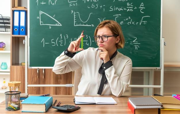 Trieste jonge vrouwelijke leraar zit aan tafel met schoolspullen die vasthoudt en kijkt naar een met potlood vastgehouden kin in de klas