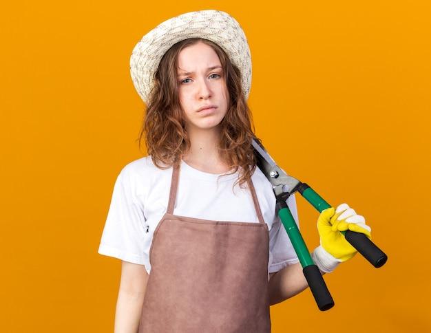 Trieste jonge vrouwelijke tuinman die een tuinhoed draagt met handschoenen die een snoeischaar op de schouder houden
