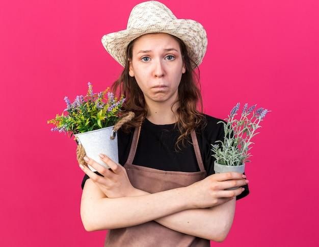 Trieste jonge vrouwelijke tuinman met een tuinhoed die bloemen vasthoudt en kruist in bloempotten