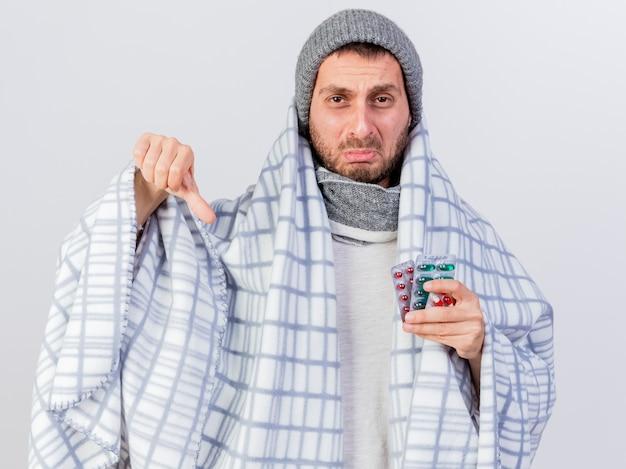 Trieste jonge zieke man met muts en sjaal verpakt in plaid bedrijf pillen