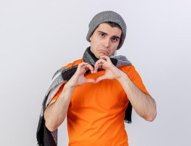 Trieste jonge zieke man met muts met sjaal hart gebaar geïsoleerd op wit tonen