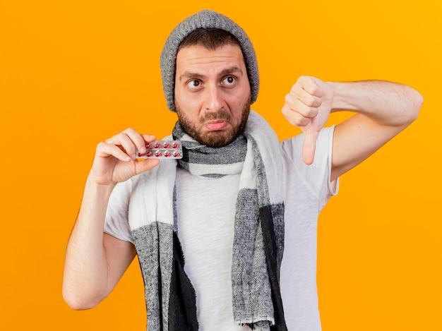 Trieste jonge zieke man met winter hoed en sjaal pillen te houden en duim omlaag geïsoleerd op gele achtergrond te tonen