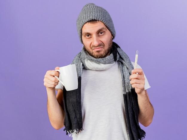 Trieste jonge zieke man met winter hoed met sjaal bedrijf thermometer met kopje thee geïsoleerd op paars