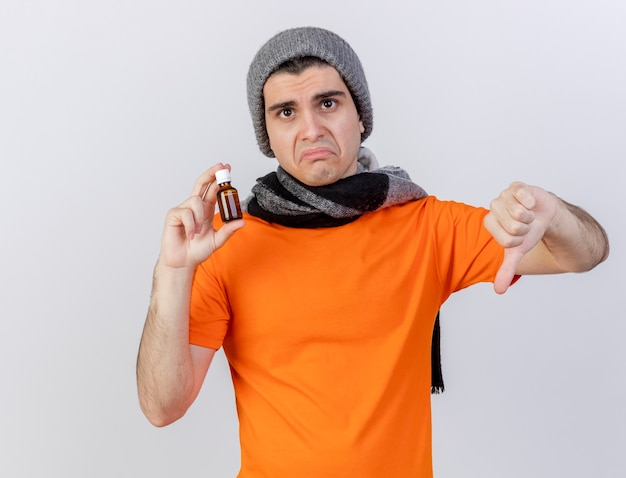Trieste jonge zieke man met winter hoed met sjaal geneeskunde in glazen fles te houden met duim naar beneden