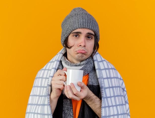 Trieste jonge zieke man met winter hoed met sjaal gewikkeld in een plaid houden kopje thee geïsoleerd op oranje