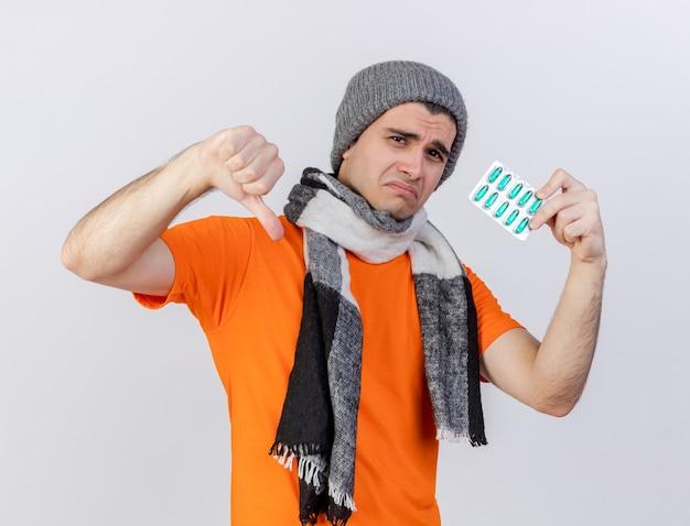 Trieste jonge zieke man met winter hoed met sjaal pillen te houden en duim omlaag geïsoleerd op wit te tonen