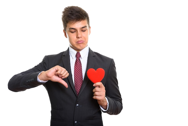 Trieste jongeman die duim naar beneden geeft terwijl hij papier hart vasthoudt en kijkt. onbeantwoorde liefde concept