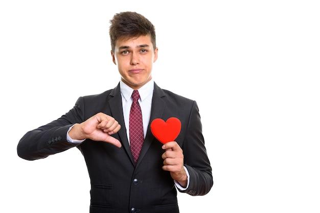 Trieste jongeman die duim omlaag geeft terwijl hij rood papier hart vasthoudt. onbeantwoorde liefde concept