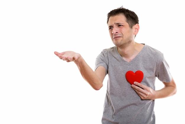 Trieste jongeman hand geven met rood hart op de borst