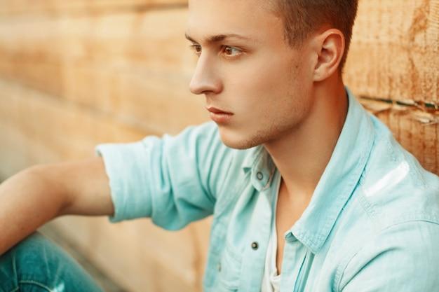 Trieste jongeman in denim kleding op de achtergrond van een houten muur