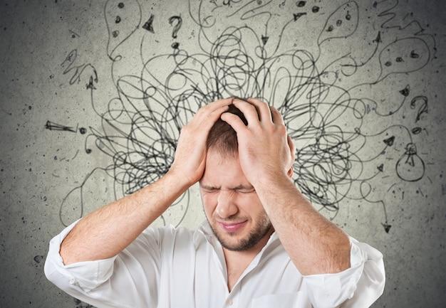 Trieste jongeman met bezorgde gestresste gezichtsuitdrukking en hersenen die in vraagtekens van lijnen smelten.
