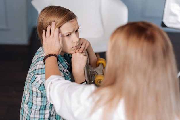 Trieste jongen die vrijetijdskleding draagt die zijn voorhoofd rimpelt terwijl hij op psycholoog kijkt
