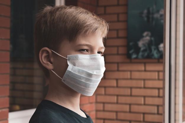 Trieste jongen in medisch masker kijkt uit het raam naar de straat