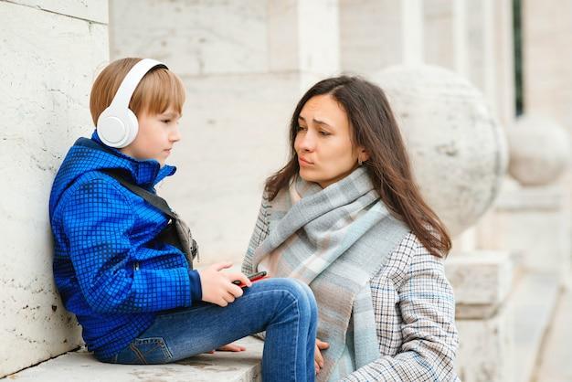 Trieste jongen luistert muziek op een wandeling. moeder en zoon samen tijd buitenshuis doorbrengen.