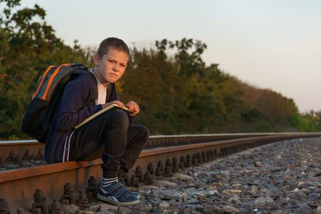 Trieste jongen met een boek in zijn handen zit op de spoorlijn. banier