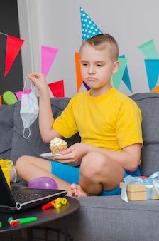 Trieste jongen met geneeskunde gezichtsmasker viert verjaardag door video-oproep naar laptop