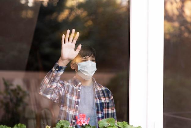 Trieste jongen met gezichtsmasker bij buitenshuis kijken
