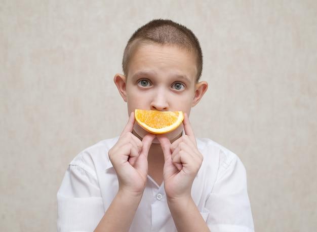 Trieste jongen met ronde ogen en een sinaasappel in plaats van een mond
