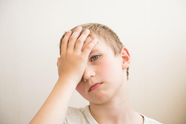 Trieste jongen sluit zijn ogen. portret. detailopname