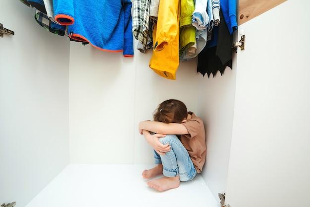 Trieste jongen verstopt in de kledingkast