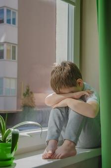 Trieste jongen wil op straat lopen, het kind staat op de vensterbank en huilt. quarantaine (zelfisolatie) door coronovirusinfectie