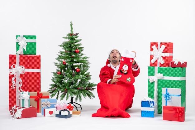 Trieste kerstman kijkt boven zittend op de grond en houdt kerstsok in de buurt van geschenken en versierde nieuwe jaarboom op witte achtergrond