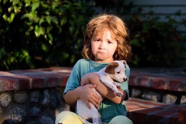 Trieste kinderen met chihuahua gemengde hond. kid omhelst liefdevol zijn hond.