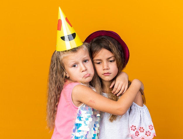 Trieste kleine mooie meisjes met feestmutsen die elkaar knuffelen geïsoleerd op een oranje muur met kopieerruimte