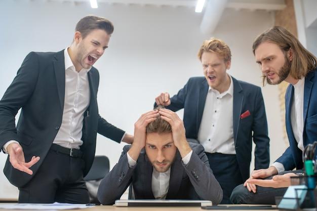 Trieste man aan de tafel die zijn hoofd vasthoudt en collega's die in de buurt staan en beschuldigend schreeuwen