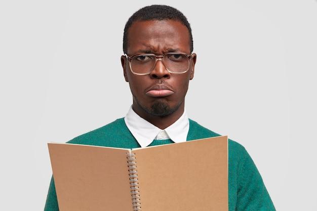 Trieste man blogger maakt aantekeningen voor publicatie, draagt notitieblok, draagt grote ongemakkelijke bril, portemonnees lip, heeft een ontevreden gezichtsuitdrukking