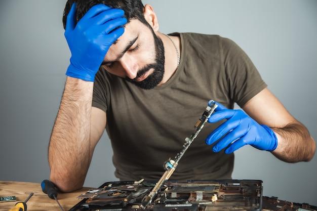Trieste man computer aan tafel repareren