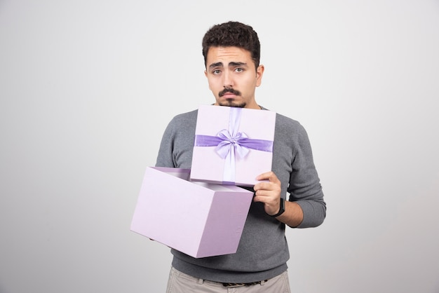 Trieste man die een paarse doos opent over een witte muur.