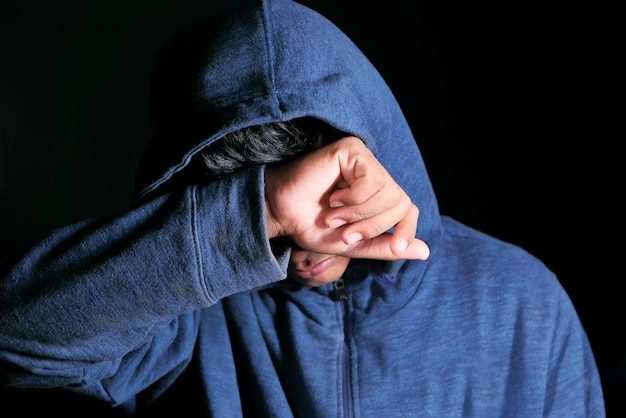 Trieste man in kap gezicht met handen geïsoleerd in het zwart