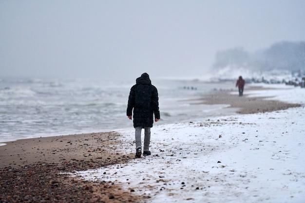 Trieste man in zwarte jas wandelen langs de zeekust in de winter. bewolkt, besneeuwd zeegezicht. eenzaamheid, scheiding, uiteenvallen concept.