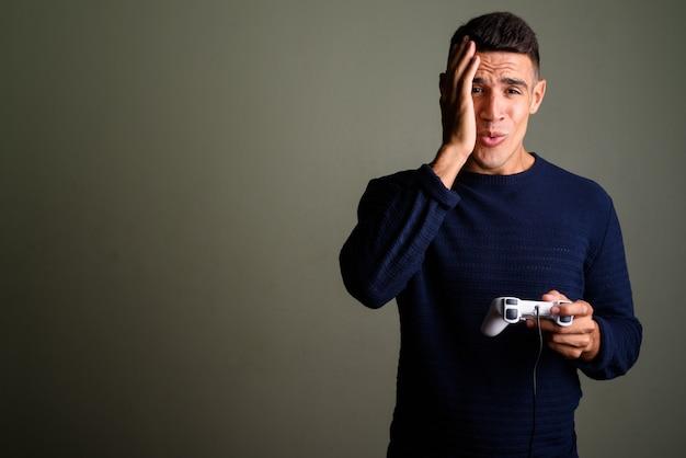 Trieste man spelen van videogames met spelbesturing tegen gekleurde achtergrond